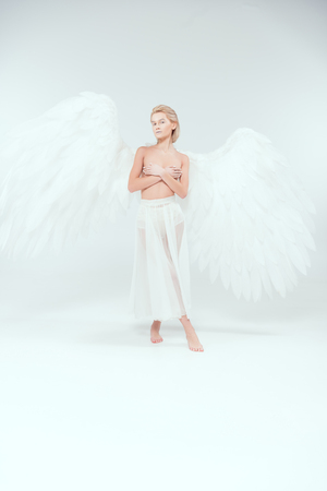 beautiful woman with angel wings covering breasts and posing while looking at camera on white background Stock Photo