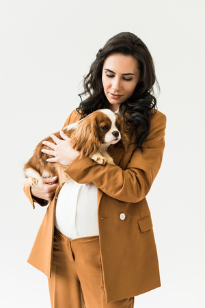 Curly pregnant woman in brown suit holding dog isolated on white Stock Photo