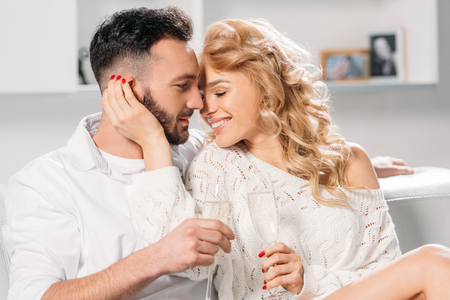 Blissful smiling couple drinking champagne at home