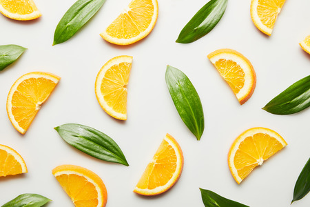 Top view of orange slices and green leaves on white background