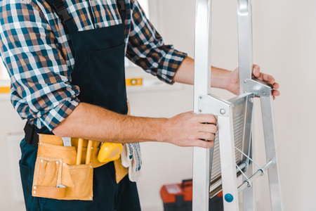 cropped view of handyman holding ladder in room Stockfoto