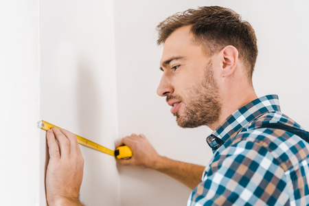 handsome handyman standing and holding measuring tape near wall