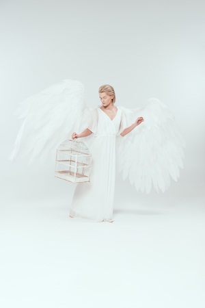 beautiful woman in angel costume with wings holding bird cage isolated on white Imagens - 119042077