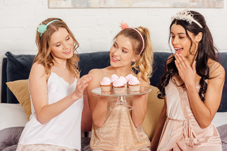 beautiful happy multicultural girls in nightwear and headbands with cupcakes during pajama party