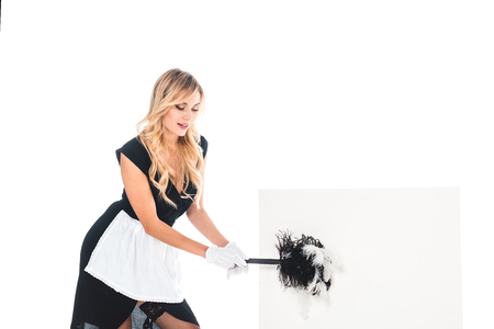 attractive housemaid in black uniform, apron, stockings sweeping with broomisolated on white placard isolated on white