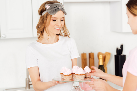 beautiful smiling girl in sleeping mask and pajamas holding glass stand with cupcakes