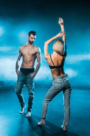sensual couple in jeans and underwear posing on blue smoky background
