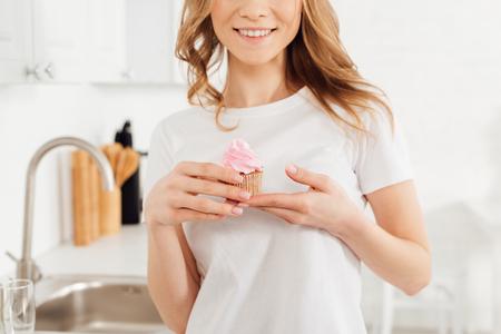 cropped view of smiling girl in pajamas holding pink cupcake in kitchen