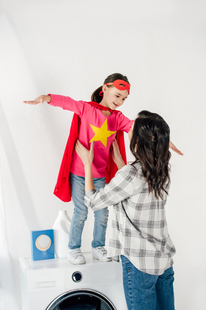 mother in grey shirt touching daughter in red homemade suit with star sign on washer in laundry room Stock Photo