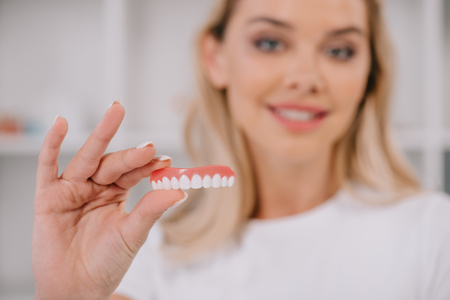 selective focus of teeth cover with smiling woman on background 写真素材 - 118997075