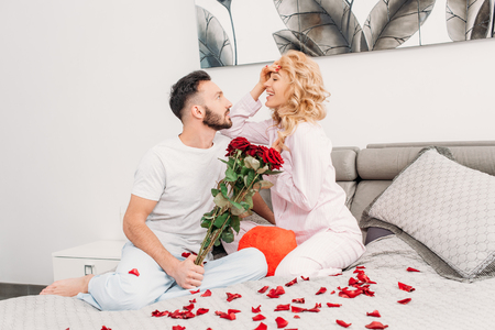 Smiling romantic couple sitting on bed with red roses Stock Photo