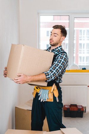 handsome handyman holding box while standing in room Stockfoto