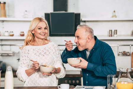 attractive wife holding bowl with cornflakes near cheerful husband eating in kitchen