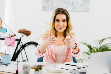 Excited blonde young woman showing thumbs up at workplace