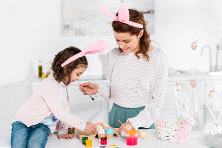 Mother and daughter in bunny ears painting easter eggs in kitchen