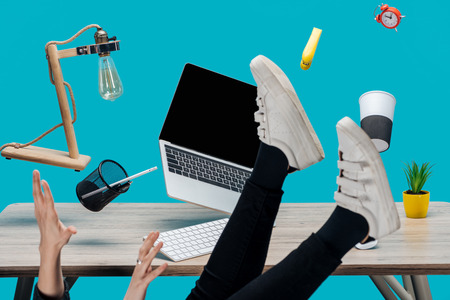 cropped view of woman levitating in air with laptop and stationery at workplace isolated on turquoise Foto de archivo