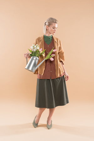 attractive girl in eco clothing holding watering can with flowers on beige background, environmental saving concept