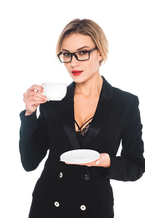businesswoman in black formal wear with open neckline and glasses drinking from cup isolated on white
