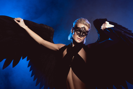beautiful sexy woman with lace mask and black angel wings looking at camera while posing on dark blue background