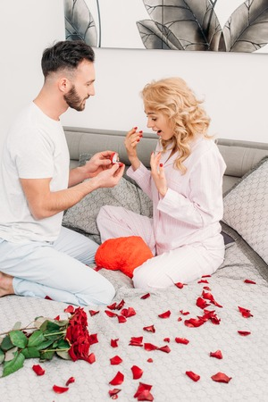 Man sitting on bed with rose petals and proposing to curly girl