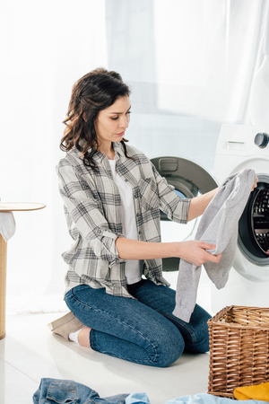 woman in grey shirt and jeans holding clothes near washer in laundry room