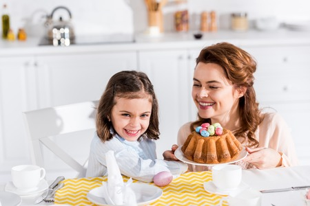Laughing mother and daughter serving table with easter in kitchen