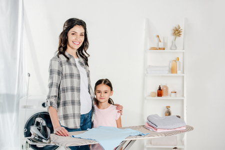 mother and daughter standing near ironing board in laundry room