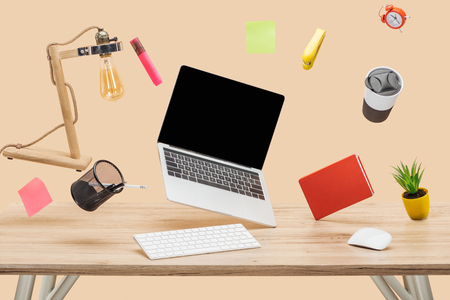 laptop with blank screen, lamp, sticky notes and stationery levitating in air above wooden desk isolated on beige