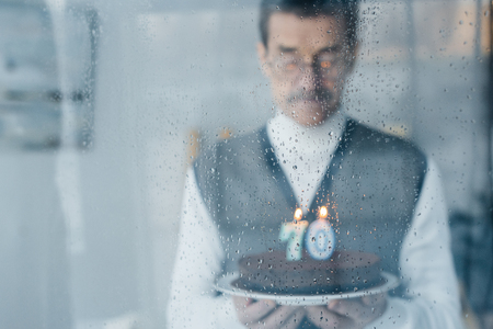 selective focus of window with raindrops with sad senior man holding birthday cake on background 스톡 콘텐츠