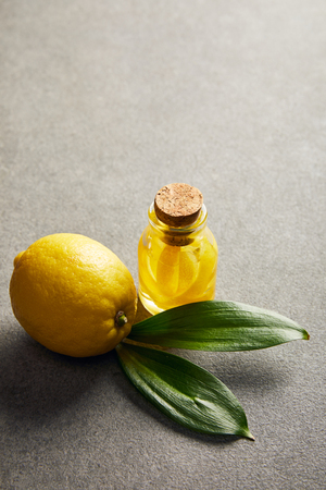 Whole lemon with green leaves and glass bottle with essential oil on dark surface