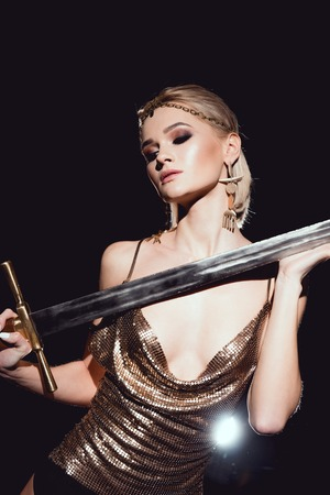 beautiful woman in golden accessories and warrior costume posing with sword on black background
