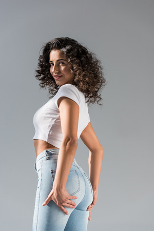Curly shapely girl in jeans touching booty isolated on grey Stock Photo