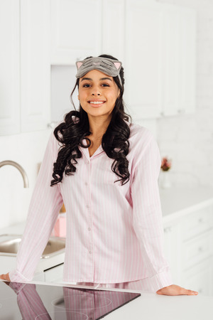 beautiful smiling african american girl in sleeping mask near induction cooker in kitchen looking at camera Stock Photo
