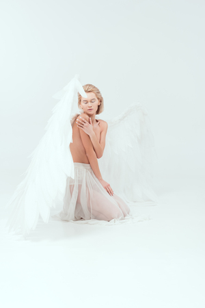 beautiful young woman with angel wings sitting and posing isolated on white