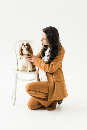 Pregnant woman sitting near chair and stroking dog on white background