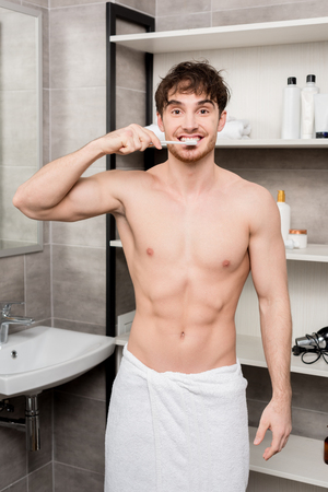 handsome man in towel brushing teeth and looking at camera 版權商用圖片