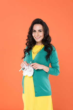 Brunette pregnant woman holding baby shoes with smile isolated on orange Stockfoto