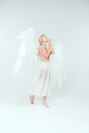 beautiful tender woman with angel wings gesturing with hands and posing isolated on white