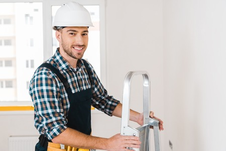 cheerful handyman in helmet smiling while holding ladder Stockfoto