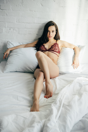 sexy brunette young woman in lingerie lying on bed Reklamní fotografie