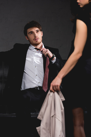 selective focus of handsome man sitting on couch and taking off tie wile brunette woman standing opposite on dark background
