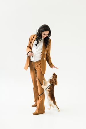 Smiling pregnant woman in brown suit playing with dog on white background