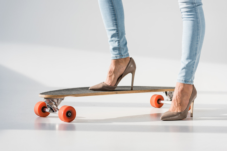Cropped view of woman in jeans and high-heeled shoes standing on lonboard on grey background Stock Photo