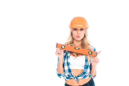 blonde architect woman in blue shirt and orange hardhat holding spirit level isolated on white Stockfoto