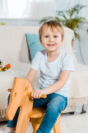 adorable smiling preschooler boy riding rocking horse at home and looking at camera
