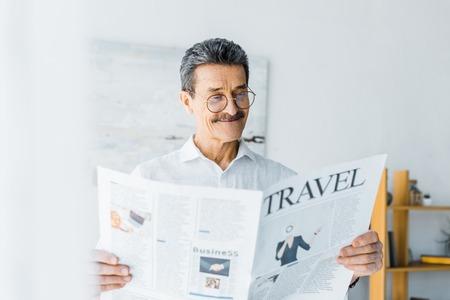 cheerful senior man reading travel newspaper at home