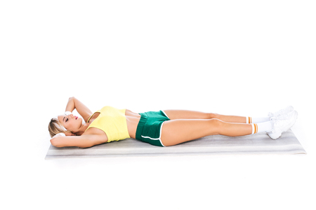 blonde fitness trainer in sportswear exercising on yoga mat isolated on white