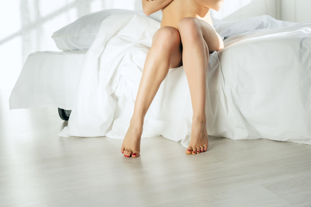 cropped view of sexy naked woman sitting on bed Standard-Bild - 119060996