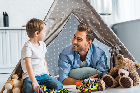 smiling father and preschooler son playing with toy cars and teddy bears under wigwam at home