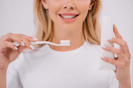 cropped view of smiling woman holding toothbrush and toothpaste with copy space isolated on white